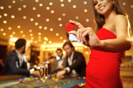 Beautiful girl holding a chip in her hand in a casino against the background of roulette poker. 스톡 콘텐츠