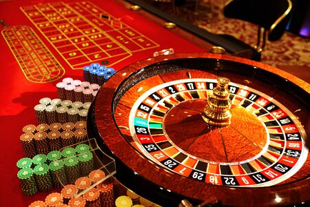 Roulette at the casino. The table is red for playing roulette.Casino concept. Stock Photo