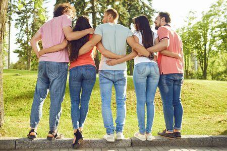 Grupos de amigos se abrazan en el parque en la naturaleza. Vista trasera.
