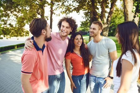 Young friends have fun talking on the street in summer spring. Stock Photo