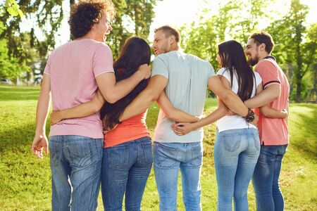 Young people hug in the park in nature. Back view. Stock Photo