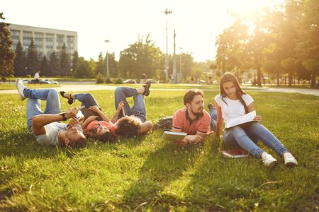 Young people are laughing while lying on the grass with books in their hands. Students read books in the park.