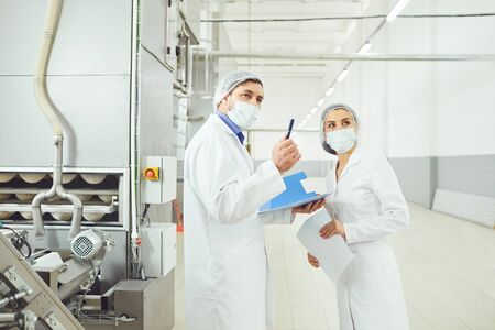 People technologists inspector in masks at food factory.