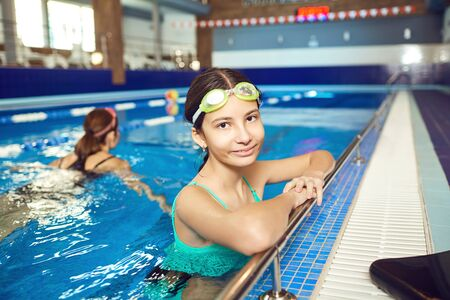 Little girl kid smiling at swimming pool indoors.