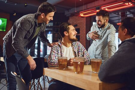 Friends talk, drink beer in a bar. Young people in a meeting in a pub. Stockfoto - 128462611