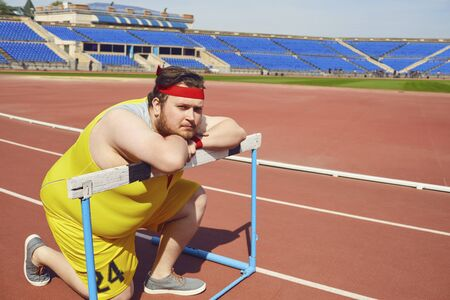 Fat funny man sitting down resting on the track in the stadium.