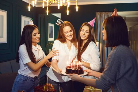Girlfriends congratulate with cake and candles for a birthday party at home Stockfoto