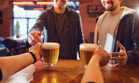 Hands of anonymous barman giving two mugs of fresh beer to crop men in pub 스톡 콘텐츠