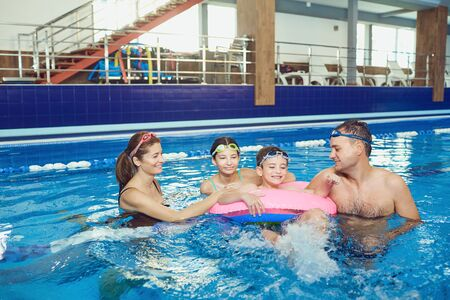 A happy family swims in a swimming pool indoors. Healthy lifestyle.