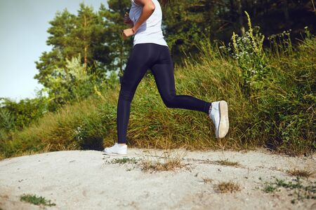 Girl runner runs along in nature in summer. Jogging in the morning. Active lifestyle. Zdjęcie Seryjne