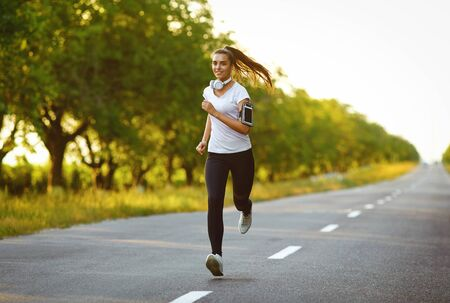 Girl runner runs along the road in summer. Jogging in the morning. Active lifestyle.