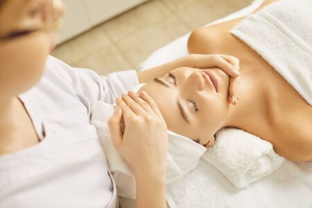 Face woman massage relax close up. Facial massage to a beautiful girl lying in a beauty clinic.Cosmetology skin care.