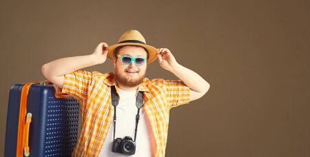 Fat funny man with a beard in a summer shirt in a hat with a suitcase smiling goes on a gray background. The original concept of recreation, travel in the summer.
