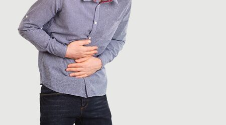 A person suffers from abdominal pain. Abdominal pain. The guy in the seeming clothes holding belly with hands.