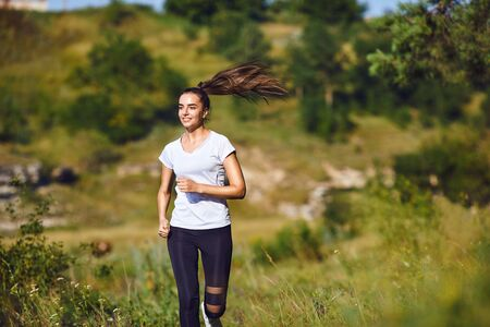 Girl runner runs along in nature in summer. Jogging in the morning. Active lifestyle.