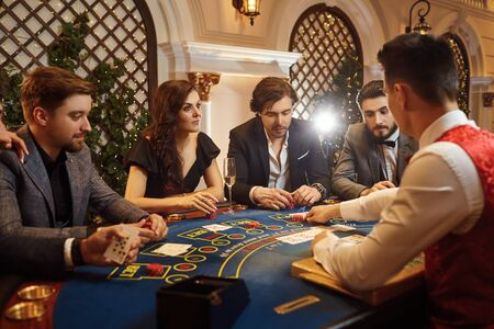 A group of people playing poker roulette at a table in a casino.