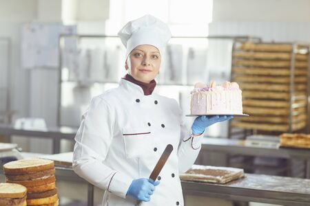 Woman confectioner with pastry cake in his hand smiling at the bakery. Фото со стока