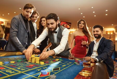 A young man with friends makes bets on roulette in a casino. Gambling in a casino.