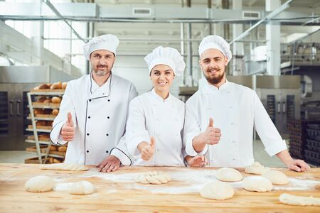 Bakers raised their thumbs up on the background of the bakery. Stockfoto - 128461899