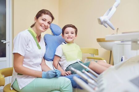 Smiling woman working as dentist sitting in office with little boy in chair both looking at camera Stockfoto - 128461927