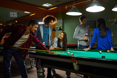 Young people play billiards. A group of young people playing fun billiards.