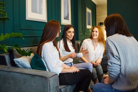 Young content women sitting on sofa at home having tea and chatting in leisure