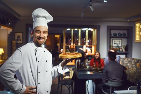 A male cook is smiling against the background of people at a table in a restaurant.