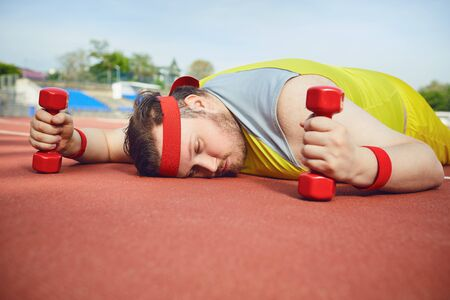 Fat lazy man sleeps tired lies on the track in the stadium. The concept of losing weight, diet.