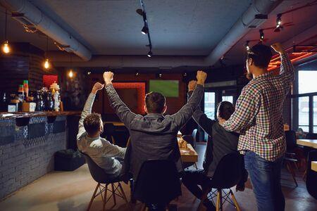 Vrienden in de sportbar ondersteunen hun team bij het tv-kijken. Stockfoto