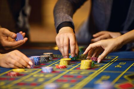 Chips in the hands of a player in a casino. Gambling poker roulette in casino. Stockfoto - 127870083