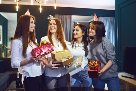 Group of cheerful beautiful women standing together with gifts while having birthday party Stockfoto - 127870095