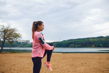 Girl in sportswear does warm-up in the park on a cloudy day. 스톡 콘텐츠