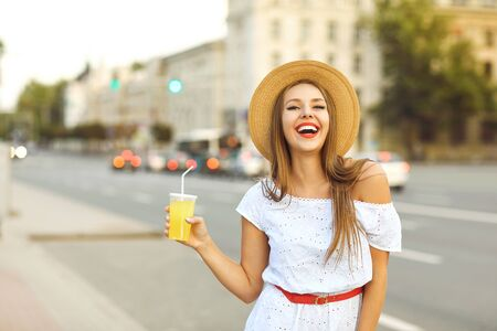 Beautiful blonde girl in a hat with a drink in hand on the street of a European city. Stockfoto - 127870098