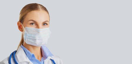Ärztin, die eine Maske vor einem grauen Hintergrund trägt.