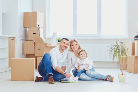 Happy couple unpacking cardboard boxes at new house at moving day. Stockfoto