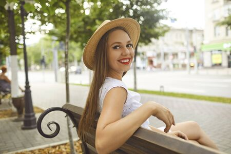 The girl in the hat smiles sits on a bench on a city street. Positive young woman portrait. 스톡 콘텐츠