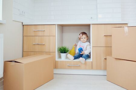 The child unpacks the boxes in the new house at moving day.