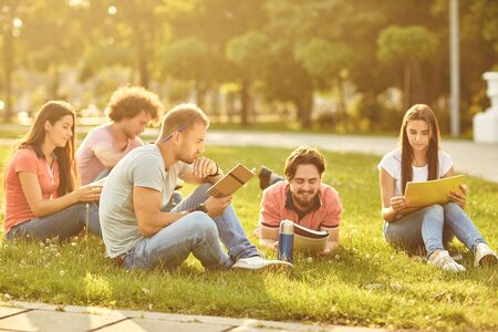 A group of students studying books sitting on the grass at sunset in a city park. Students read books in the park.