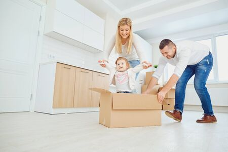 Happy family unpacking cardboard boxes at new home at moving day. Stockfoto