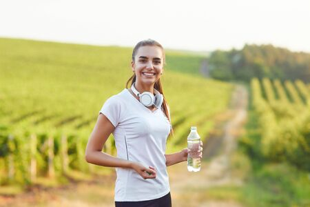 Brunette girl runner with a bottle of water is in training against the background of vineyards. Active lifestyle. Stockfoto - 127794827