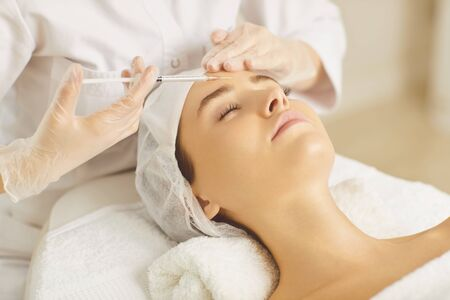 Cosmetology doctor makes beauty injections on face to a woman in a beauty salon. Stockfoto