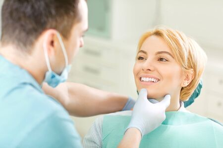 Dentist looking the teeth of the patient girl sitting in a chair in the dental clinic. Stockfoto - 127794825