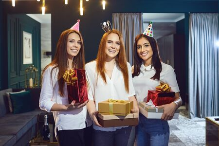 Cheerful women congratulating friend on birthday and giving gift boxes gathering at home Stockfoto - 127794823