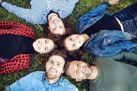 View from above. Friends lie on the grass in the park.