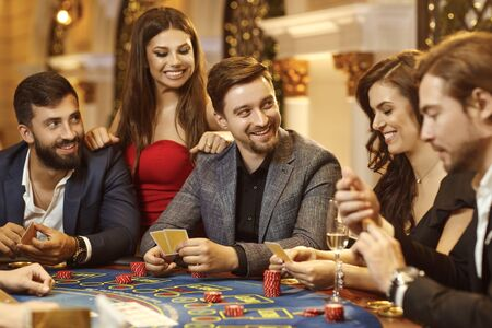 A group of people playing gambling in a casino.