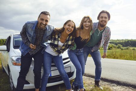 A group of friends travelers laughing near the car by the road.