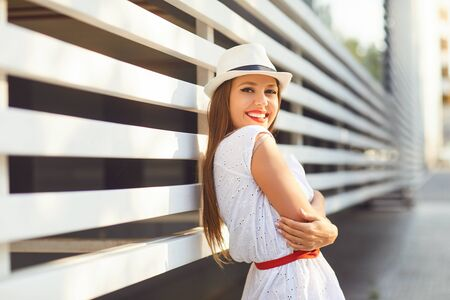A girl with a beautiful smile is laughing on striped background a city street.