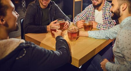 Cheerful friends raised their hands above the table with glasses and beer in the bar. Meet the young people in the pub.