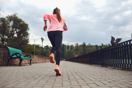The girl in sportswear runs along the road in the park. Back view. Jogging in the morning. Active lifestyle. Stockfoto