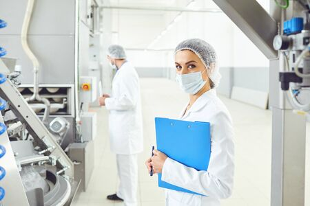 A woman in a mask in a white uniform with a folder in her hand controls the production process.